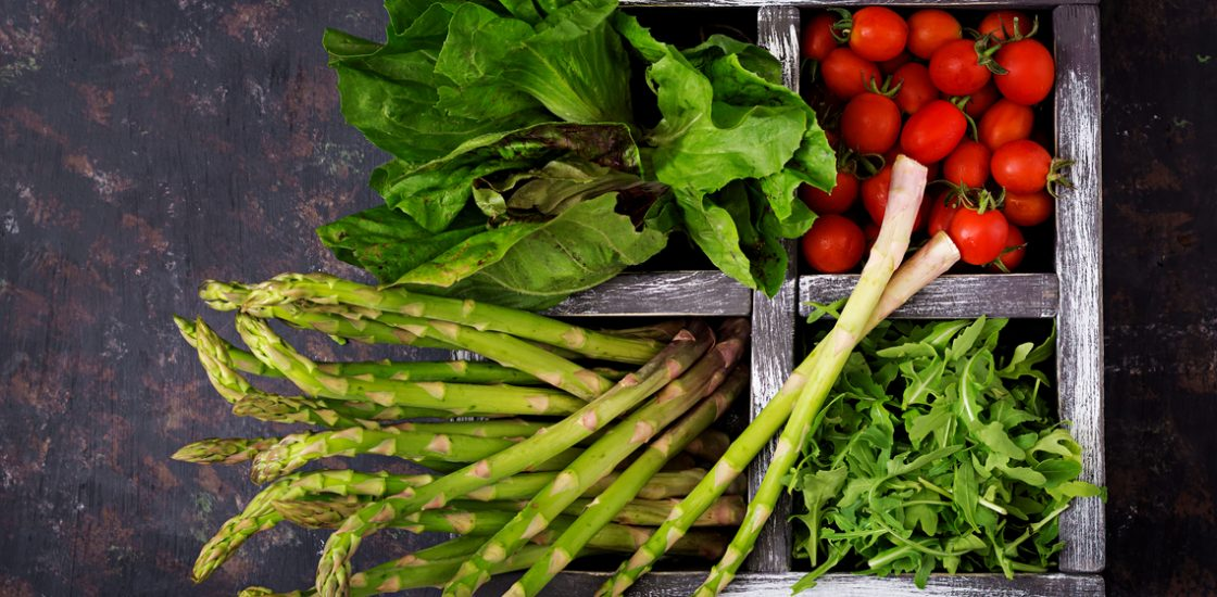 Fresh asparagus, tomato. arugula and lettuce in wooden box  on dark background