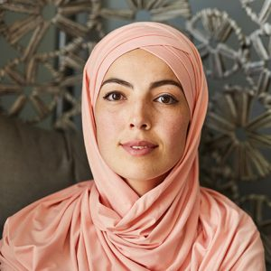 Portrait of young beautiful Muslim woman in light peach hijab smiling at looking at camera